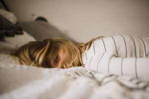 A stressed woman lying on a bed. How to stay sane during COVID-19 :: Albuquerque Moms Blog